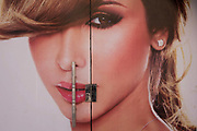 The face of a beauty model is spread across two doors of a business in the modern city of Luxor, Nile Valley, Egypt. Across her mouth is the vertical door handle seemingly a piercing over her lips.