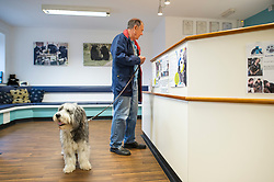 A dog and his owner in reception, Rushcliffe Veterinary Centre, West Bridgford, Nottingham, UK.<br />
