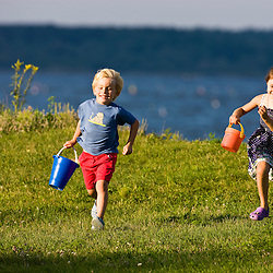 A young brother and sister running in Odiorne State Park in Rye, New Hampshire.