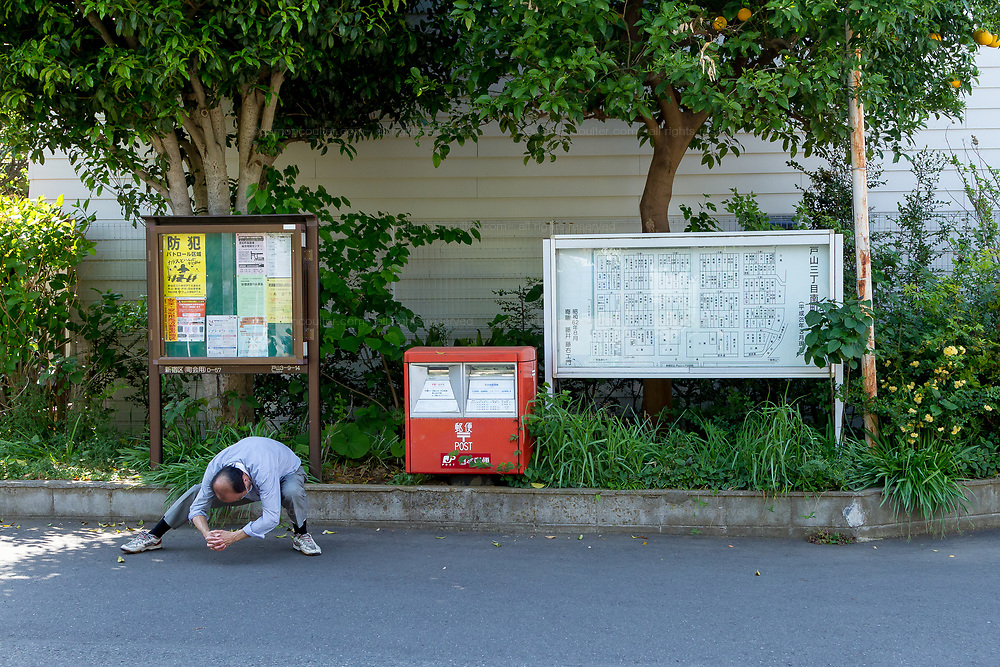 A man does stretching exercises in the street in a quiet corner of Shinjuku, Tokyo, Japan Friday April 20th 2018