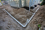 Poly Vinyl Chloride (PVC) Pipes being installed for rainwater harvesting system at new home construction. System is gravity based and relies on a 2% grade to carry captured water to cisterns or rain barrels in backyard. Los Angeles, California, USA