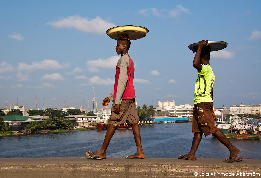 Nigeria - Male hawkers carrying their wares and walking on the edge of a bridge