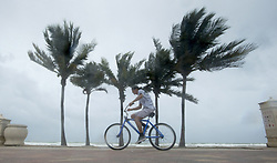 September 9, 2017 - Hollywood, FL, United States - A man rides his bike along the beach with blowing winds and threatening skies in anticipation for Hurricane Irma, in Hollywood, Fla., Saturday, September 9, 2017. THE CANADIAN PRESS/Paul Chiasson (Credit Image: © Paul Chiasson/The Canadian Press via ZUMA Press)