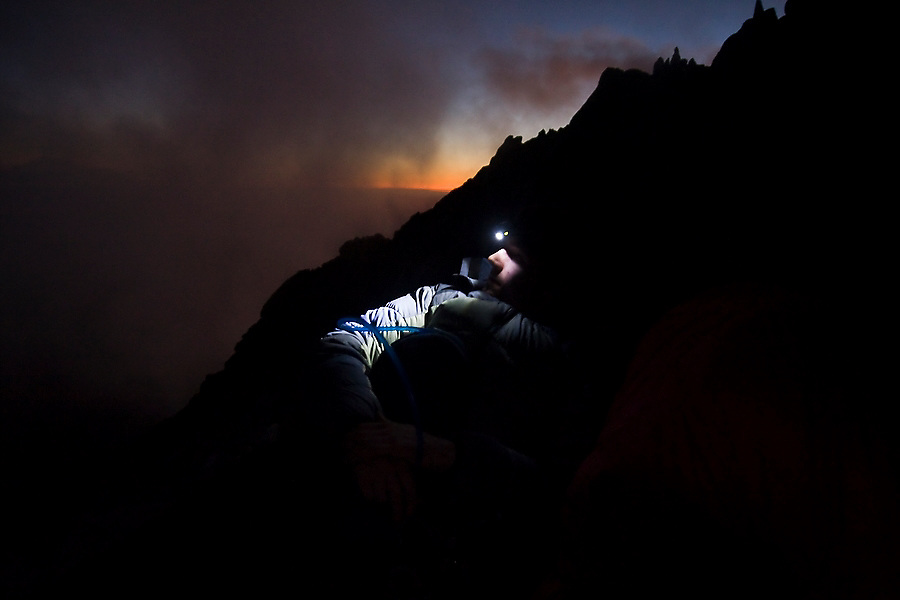 Climber Kris Haskins waits for night to fall at a bivy below the summit of Mount Stuart in the Alpine Lakes Wilderness, Washington.