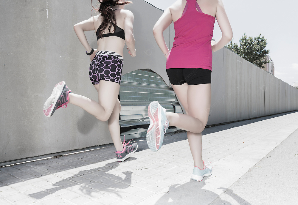 Two young women running in the city