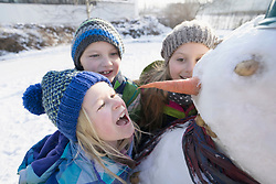 Children with snowman on snow field
