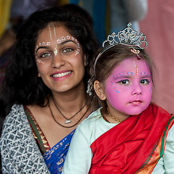 © Licensed to London News Pictures. 05/09/2015. Watford, UK. A make-up artist sits with Kishori, aged 4, who wears a crown and pink face-paint with gopi dots during her visit to the biggest Janmashtami festival outside of India at the Bhaktivedanta Manor Hare Krishna Temple in Watford, Hertfordshire.  The event celebrates the birth of Lord Krishna and the festival  includes music, dance, food, dramas and more. Photo credit : Stephen Chung/LNP