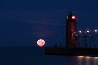 The full moon melts into Lake Michigan in the early morning as early-risers look on.