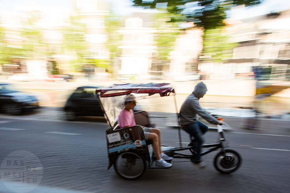 In Amsterdam rijdt een toerist mee met de fietstaxi.<br /> <br /> In Amsterdam a tourist is riding with a bike taxi.