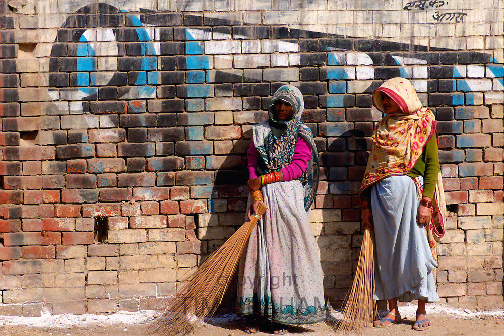 Women sweeping the street in Agra, India.