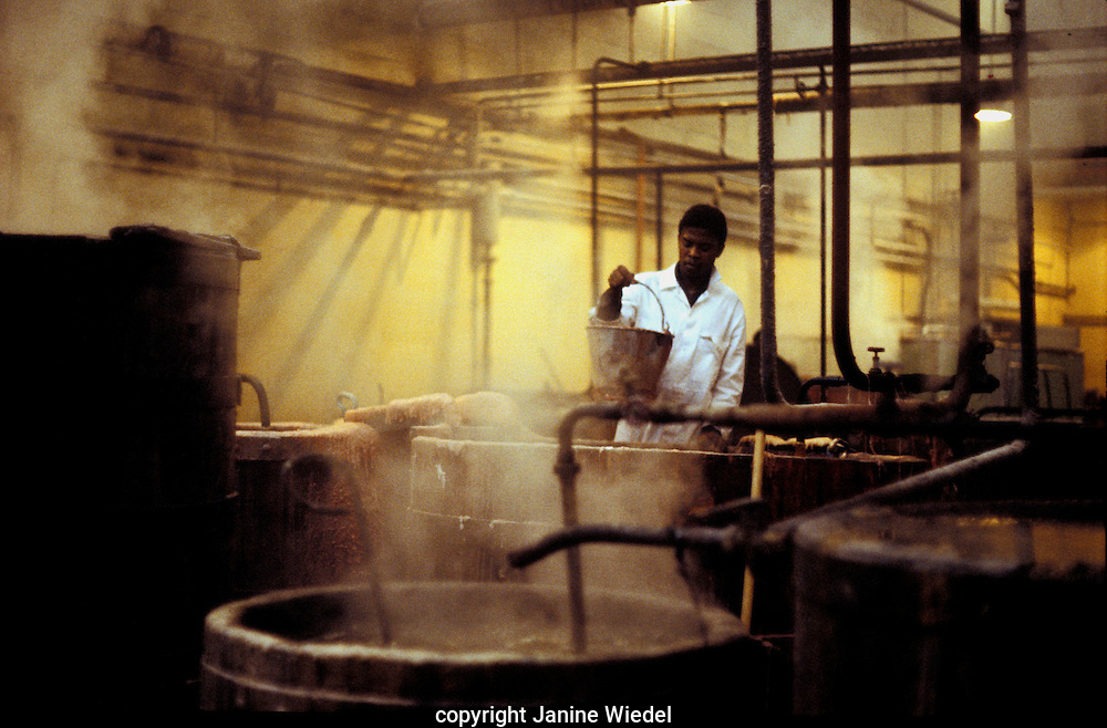 factory worker warming up vats of wax at Prices candle  firm in  South London .1970s