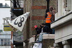 © London News Pictures. 11/06/2013. London, UK.  Anti-G8 activists on the roof of an abandoned police station used as their headquarters, which is surrounded by police,  ahead of a demonstration in central London today (Tues) The G8 Summit is due to take place in Norther Ireland early next week.  Photo credit: Ben Cawthra/LNP