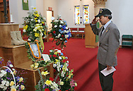 Allen Hoe father of 1st Lt. Nainoa K. Hoe, 27, of Hawaii salutes a photo of his son who died in Iraq, after a memorial main Post Chapel at Ft. Lewis Wash. (AP Photo/John Froschauer)