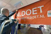 Nederland, Winssen, 16-3-2019In de regio vinden veel activiteiten plaats in het kader van de NLdoet actiedag. Het NLDoet spandoek hangt bij een activiteit in het dorpshuis. De muren worden gewit .Foto: Flip Franssen