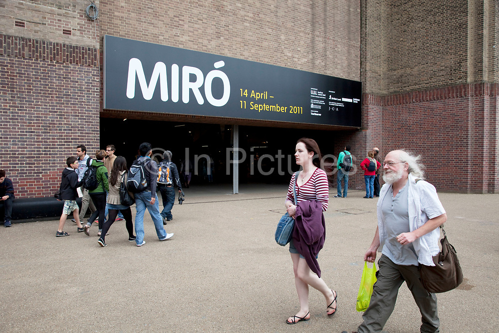 People passing Miro poster outside Tate Modern gallery, London. The artists MIro is having a large retrospective exhibition here and proving incredibly popular. Joan Miró i Ferrà (April 20, 1893 – December 25, 1983) was a Spanish Catalan painter, sculptor, and ceramicist born in Barcelona.