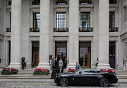 A polished black Bentley car parked outside the tall columns of the Four Seasons hotel at 10 Trinity Square in the City of London - the capitals financial district, on 4th June 2018, in London, England.