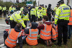 Colnbrook, UK. 27th September, 2021. Metropolitan Police officers monitor Insulate Britain climate activists who had previously blocked a slip road from the M25 at Junction 14 close to Heathrow airport and then glued themselves together as part of a campaign intended to push the UK government to make significant legislative change to start lowering emissions. The activists are demanding that the government immediately promises both to fully fund and ensure the insulation of all social housing in Britain by 2025 and to produce within four months a legally binding national plan to fully fund and ensure the full low-energy and low-carbon whole-house retrofit, with no externalised costs, of all homes in Britain by 2030.