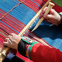 South America, Peru, Chinchero. Chinchero Cooperative weaver demonstrates using loom and tool.