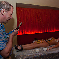 Guest takes photo of a girl during a naked sushi night where following japanese traditions sushi is served on the bodies of naked women in a club in downtown Budapest, Hungary on September 23, 2011. ATTILA VOLGYI