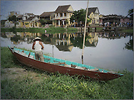 A fisherman stands in his wooden boat moored on the riverbank of Thu Bon across from the Japanese Bridge in Hoi An, Vietnam, Southeast Asia
