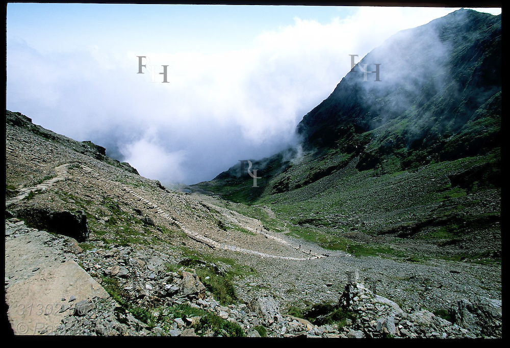 Hikers struggle up switchbacks of Pyg Track as Mount Snowdon (3560') looms in distance; Snowdonia National Park, Wales