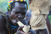Hadza man smoking from a traditional clay pipe Photographed near Lake Eyasi, Tanzania, Africa