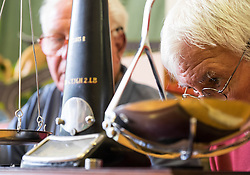 © Licensed to London News Pictures.04/08/15<br /> Egton, UK. <br /> <br /> <br /> Weigh man HARRY HEBDON checks the scales for the weight of one of the gooseberries during judging at the annual Egton Gooseberry Show. <br /> There are only two Gooseberry societies left in the country. One in Cheshire and one at Egton in North Yorkshire. The annual show in Egton uses traditional Avoridupois scales to measure the weight of the berries and members of the society are fanatical about trying to grow the best berries each year. <br /> <br /> Photo credit : Ian Forsyth/LNP