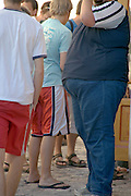 extremely obese young man standing among his not obese friends