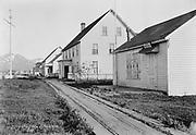 "9707-K239. written on original negative: ""Street of Unalaska CLA."" Sign on nearest building ""Office. Commanding officer. Bering Sea fleet"" The post office is the third building down. June 22-24, 1917 Alaska"