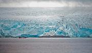 Sailboat in front of huge glacier at western coast of Spitsbergen, Svalbard in July 2012.
