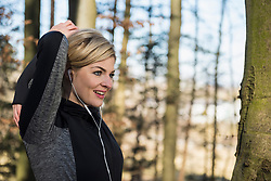 Woman with headphones stretching in forest