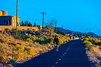 Woman biking on a path along Tramway Boulevard, Albuquerque, New Mexico USA