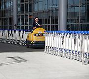 Man driving vehicle collecting trolleys at Malaga airport, Spain