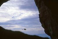 Helicóptero volando frente a la cueva del tepuy Autana, Amazonas, Venezuela.