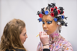 © Licensed to London News Pictures. 25/02/2019. LONDON, UK. A make-up artist applies her Disney-inspired bodypaint on a model at the Warpaint Zone at Professional Beauty, the UK's largest beauty and spa trade show, taking place at Excel London in Docklands.  Photo credit: Stephen Chung/LNP