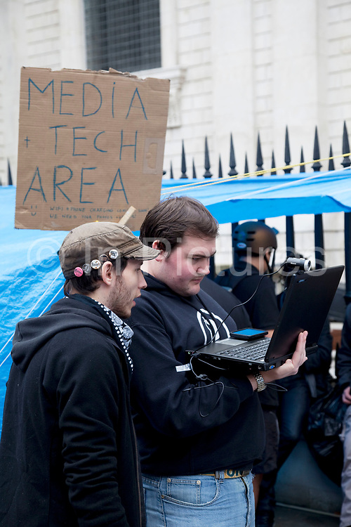 """Media Tech Area being set up to aid techinical support. Wifi coming soon! Occupy London protest at St Pauls, October 16th 2011. Protest spreads from the US with this demonstrations in London and other cities worldwide. The 'Occupy' movement is spreading via social media. After four weeks of focus on the Wall Street protest, the campaign against the global banking industry started in the UK this weekend, with the biggest event aiming to """"occupy"""" the London Stock Exchange. The protests have been organised on social media pages that between them have picked up more than 15,000 followers. Campaigners gathered outside  at midday before marching the short distance to Paternoster Square, home of the Stock Exchange and other banks.It is one of a series of events planned around the UK as part of a global day of action, with 800-plus protests promised so far worldwide.Paternoster Square is a private development, giving police more powers to not allow protesters or activists inside."""