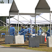 Medical personnel in full personal protective equipment wait to test residents who are aged 65 and over that are concerned they may have acquired Coronavirus (COVID-19) at the Orange County Convention Center on Friday, March 27, 2020 in Orlando, Florida. (Alex Menendez via AP)