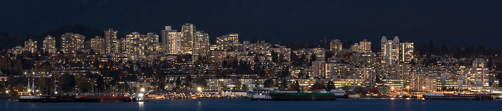 Apartment and condo towers on the hillside of North Vancouver with various barges and ships in Burrard Inlet below.  Photographed from Stanely Park in Vancouver, British Columbia, Canada.