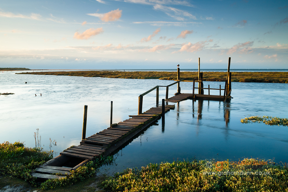High tide waters almost engulf an old wooden jetty at Thornham Harbour, North Norfolk, East Anglia.