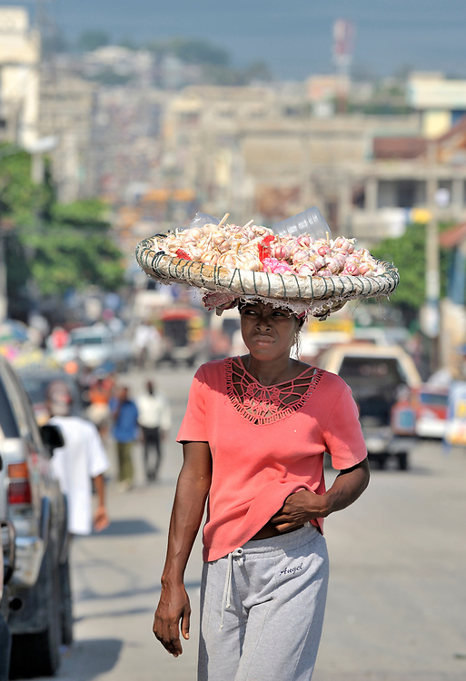 A woman carries items to sell in the market in the Bel-Air neighborhood of Port-au-Prince, Haiti.