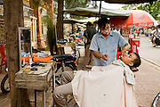 29 JUNE 2006 - PHNOM PENH, CAMBODIA: An open air street side barber shop in central Phnom Penh, Cambodia.  Photo by Jack Kurtz / ZUMA Press