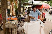 29 JUNE 2006 - PHNOM PENH, CAMBODIA: An open air street side barber shop in central Phnom Penh, Cambodia.  Photo by Jack Kurtz / ZUMA Press