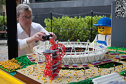 © Licensed to London News Pictures. 05/07/2012. London, UK. A man photographs a minature replica of the Olympic Park constructed from Lego. LEGO creator, Warren Elsmore used around 250,000 standard LEGO bricks to create a miniature replica of the London 2012 Olympic Games Park. The model took Warren, aged 35 from Edinburgh, 300 hours to construct and is on display at the 'Visit Denmark' Olympic Village  at St Katharine Docks, London. Photo credit : Vickie Flores/LNP