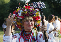 July 6, 2018 - Kiev, Ukraine - A woman poses for a selfie photo during celebration on the traditional Ivana Kupala (Ivan the Bather) holiday, an ancient heathen holiday, in Kiev, Ukraine, on 06 July 2018. The ancient tradition, originating from pagan times, is marked with grand overnight festivities during which people sing and dance around campfires, believing it will purge them of their sins and make them healthier. During the celebrations, people wear wreaths, jump over fires and bathe naked in rivers and lakes. (Credit Image: © Serg Glovny via ZUMA Wire)