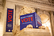 New York, NY - 3 November 2020. New York City anticipates presidential election results as polls in some states close. Patience, the statuary lion on the south end of the steps of the New York Public Library, carries a book asking people to read, think, and vote.
