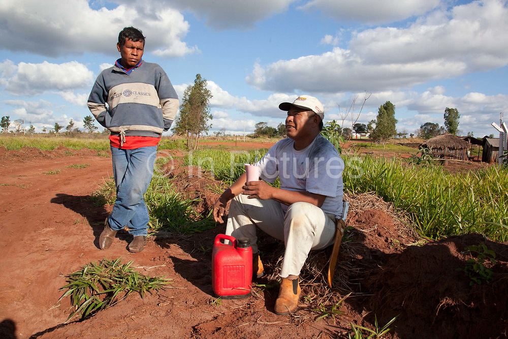 Two 2 Guarani men outdoors drinking tea and talking. The Guarani are one of the most populous indigenous populations in Brazil, but with the least amount of land. They mostly live in the State of Mato Grosso do Sul and Mato Grosso. Their tradtional way of life and ancestral land is increasingly at risk from large scale agribusiness and agriculture. There have been recorded cases and allegations of violence between owners of large farms and the Guarani communities in this region.