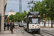 De Lijn tram travels along route 22 to Kouter on the Ghent tramway network in central Ghent, Belgium.  Belgian pedestrians and cars travel alongside the tram in the street.