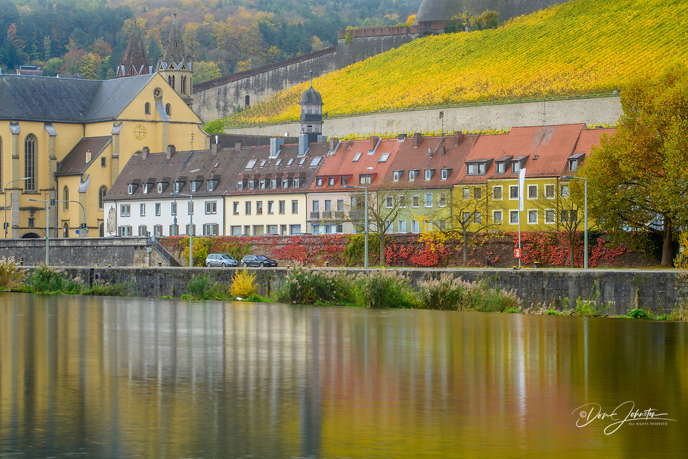 Riverside buildings and autumn vineyards below the Marienberg fortress reflected in the Main River, Wurzburg, Bavaria, Germany