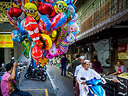01 SEPTEMBER 2017 - BANGKOK, THAILAND: Men arrive on a motorbike at the celebration of Eid al-Adha at Haroon Mosque in Bangkok. Eid al-Adha is also called the Feast of Sacrifice, the Greater Eid or Baqar-Eid. It honours the willingness of Abraham to sacrifice his son. Goats, sheep and cows are sacrificed in a ritualistic manner after services in the mosque. The meat from the sacrificed animal is supposed to be divided into three parts. The family retains one third of the share; another third is given to relatives, friends and neighbors; and the remaining third is given to the poor and needy.     PHOTO BY JACK KURTZ