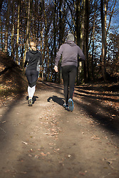 Rear view of man and woman in sportswear jogging on forest path